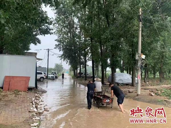 老人骑三轮陷积水中脚有伤不敢下水 热心人蹚水推车